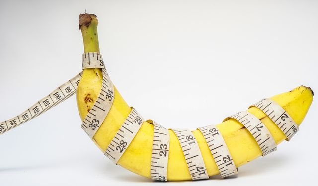 conceptual illustration for penis size, banana with plastic tailor meter on white background