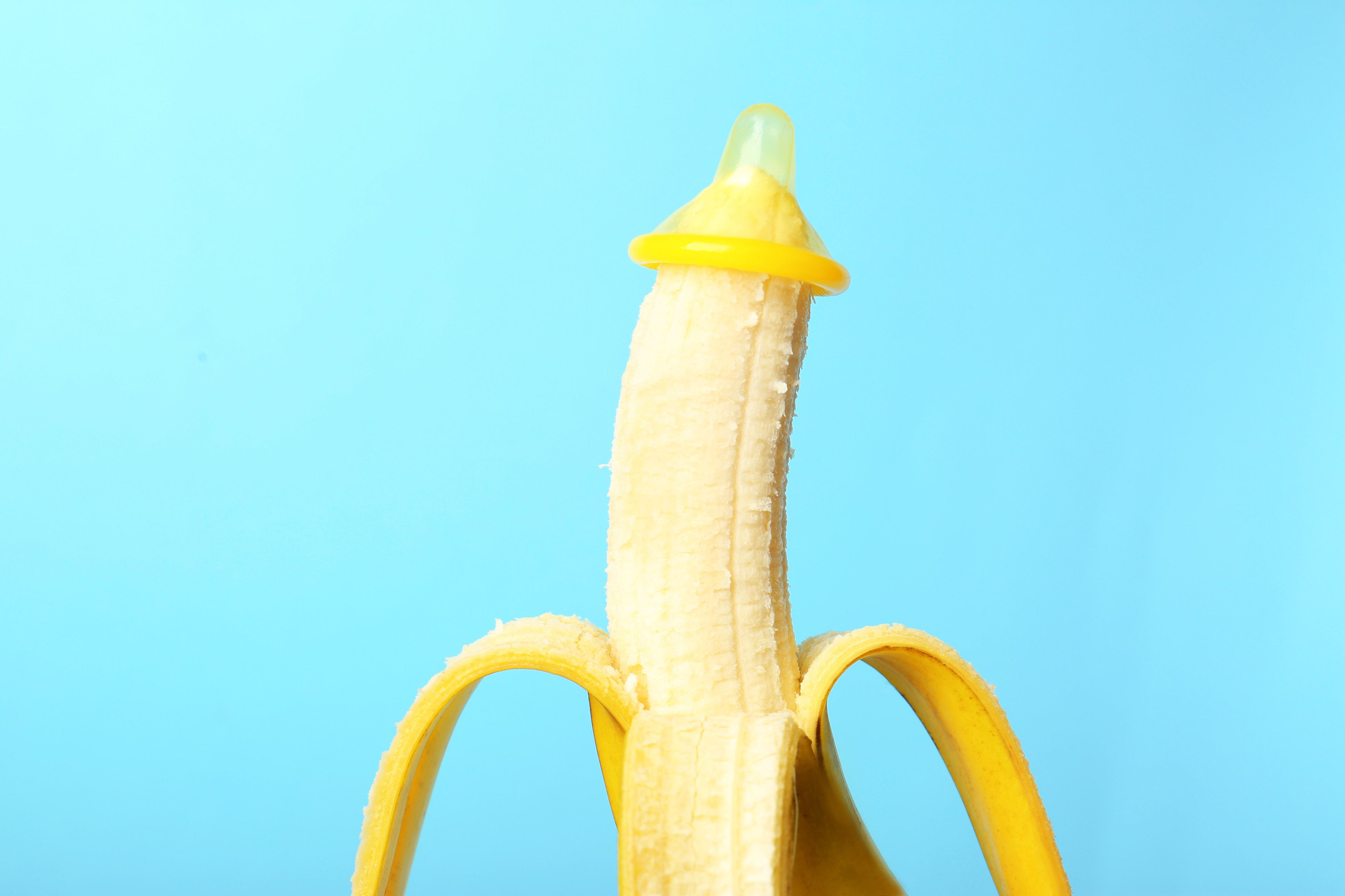 Condom on banana against color background. Safe sex concept
