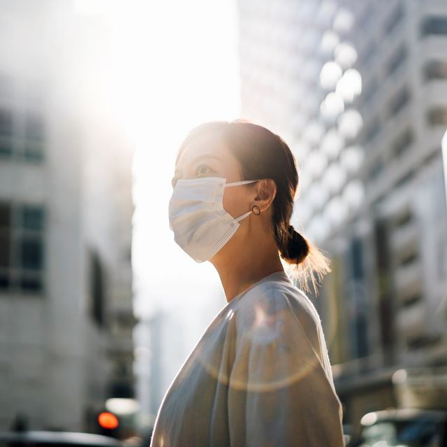 confidence and determined young asian woman with protective face mask standing in the city street, looking away with hope against beautiful lens flare in the fresh morning