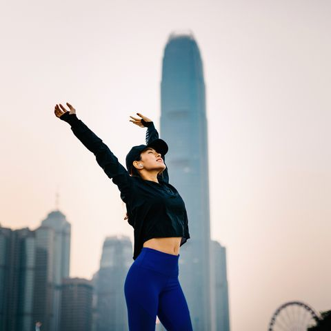 Confidence and smiling Asian sports woman stretching arms overhead outdoors against urban cityscape at sunset