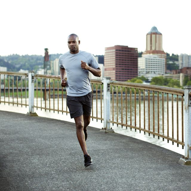 confident male athlete running on footbridge over river against clear sky in city