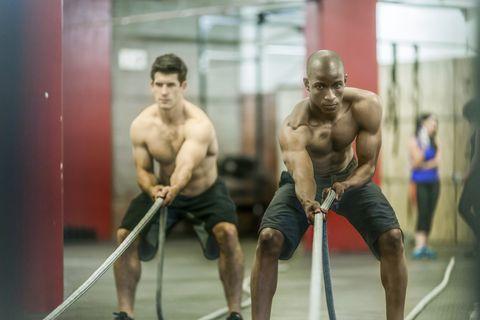 Confident male athletes doing battle rope exercise