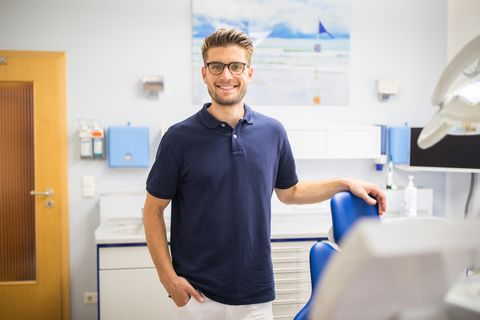 confident male dentist standing in his clinic