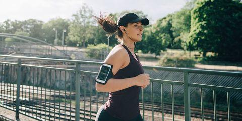 Confident sportswoman listening music through in-ear headphones while jogging on bridge in city