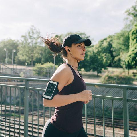 confident sportswoman listening music through in ear headphones while jogging on bridge in city