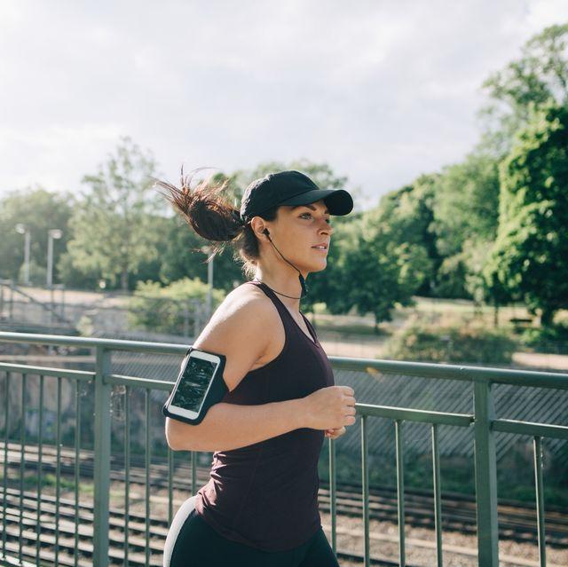 confident sportswoman listening music through inear headphones while jogging on bridge in city