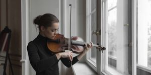 Confident woman with sheet music on window sill playing violin in mansion