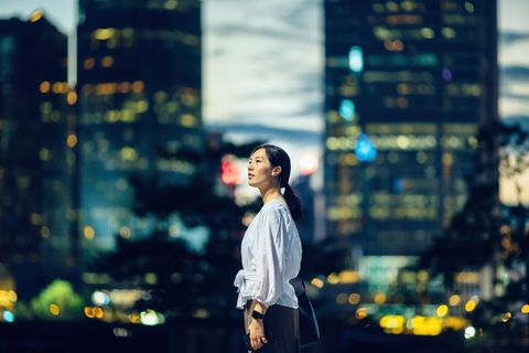 Confident young Asian woman standing against illuminated city buildings and thinking of her career path