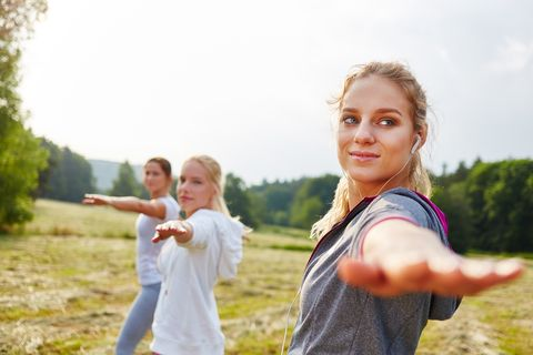 Confident Young Women Practicing Yoga In Warrior Position On Field Against Clear Sky
