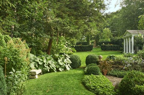 japanese pachysandra, giant butterbur, and english boxwoods form an evergreen passage from the pool garden to a potting shed and greenhouse