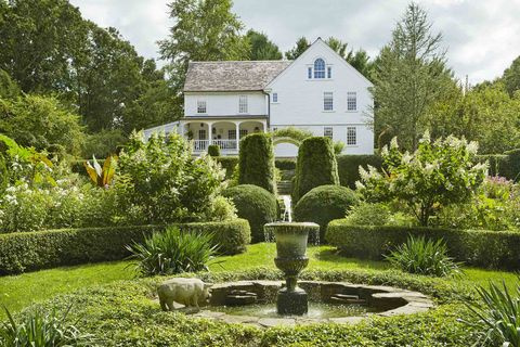 a low privet hedge forms a traditional rondel inside it, a fountain with stone from a mini quarry on the property surrounded by vinca minor ground cover a grand white farmhouse is in the background