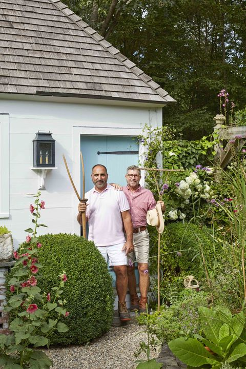 two men with gardening tools pose in from of a garden house surrounding by plants
