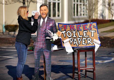 Una mujer bromea con un cartón con la imagen de Conor McGregor.