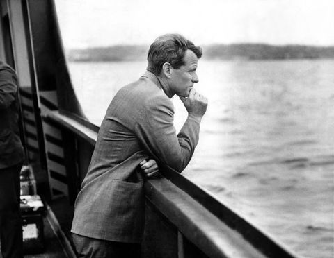 A contemplative Robert F. Kennedy leans on the railing of a