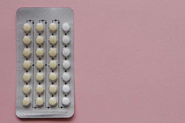 contraceptive pills in blister pack on pink background