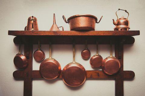 Copper Kitchen Utensils Arranged On Shelf In Kitchen