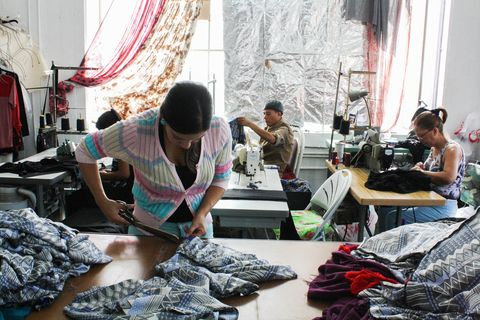 a woman cuts fabric at a warehouse, behind her other workers labor at sewing machines
