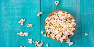 corn popcorn on a blue wooden background, as a snack for watching movies