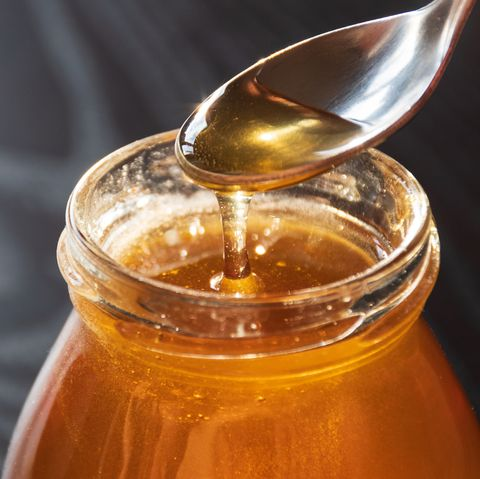 delicious organic natural bio honey pours out of the spoon into a glass jar on wooden table with reflection of the sun, black background, close up
