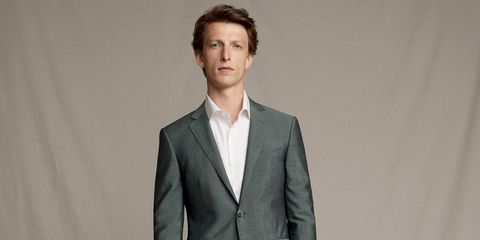 Suit, Clothing, Formal wear, White-collar worker, Blazer, Outerwear, Hairstyle, Standing, Tuxedo, Forehead,