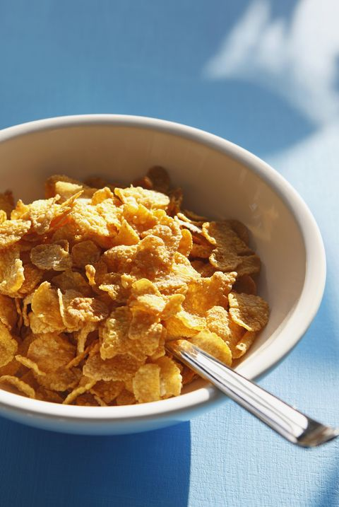 cornflakes and spoon in bowl, close up