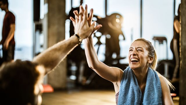 vrouw geeft high five in de sportschool