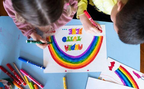 kinderen in italië maken tekeningen van een regenboog voor de zorgmedewerkers tijdens de coronacrisis