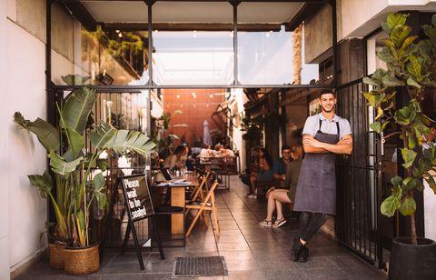 man voor restaurant   coronamaatregelen
