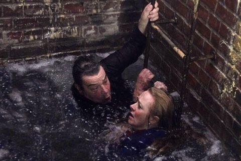 Jenny y Johnny Connor en un túnel inundado con cabezas sobre el agua sosteniendo una escalera