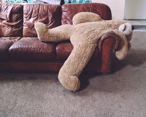 un orsacchiotto di grandi dimensioni seduto su un divano, metafora di una persona single che si masturba per stare bene