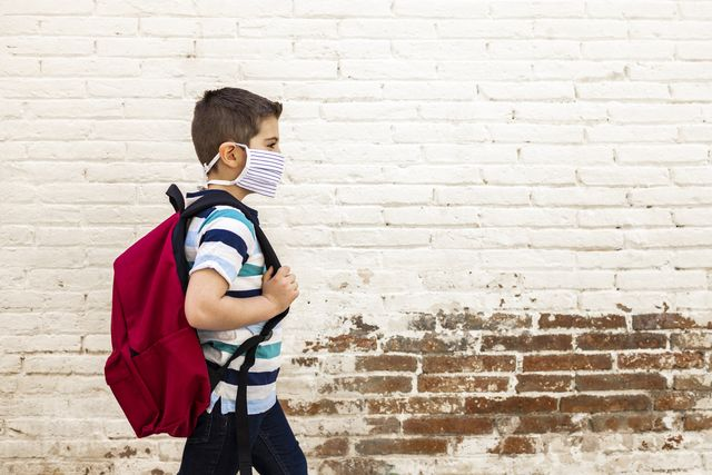 little boy going to school with protective mask