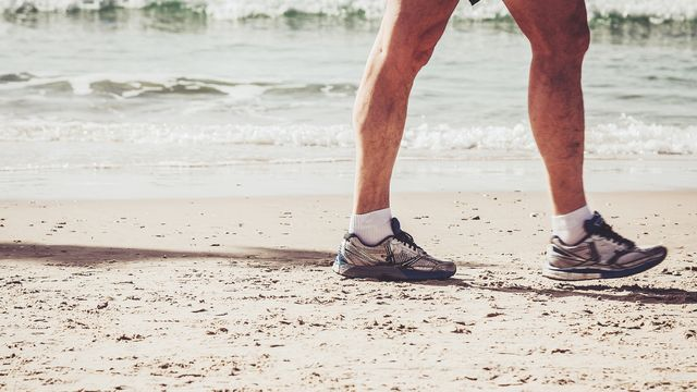 imagen de las piernas de un corredor y sus rodillas en la playa