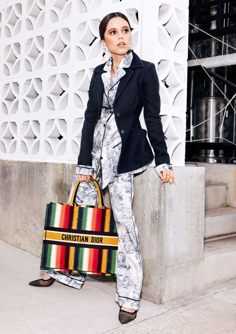 jenna ortega stands in a pajama set and blazer, belted, with a dior bag