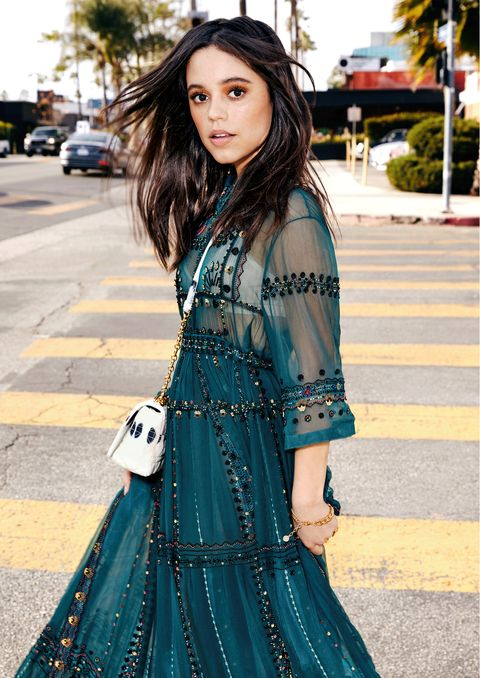 jenna ortega walks across a crosswalk wearing a long turquoise gown, looking at the camera