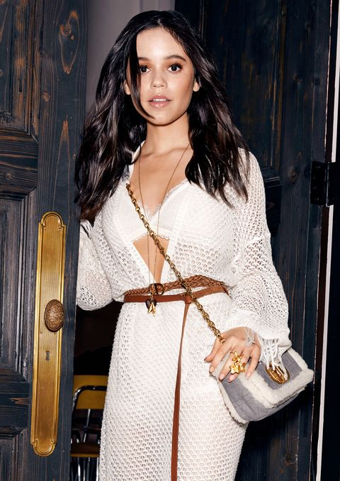 jenna ortega wears a white crochet dress, brown belt, gold jewelry, and grey bag, walking out of a doorway