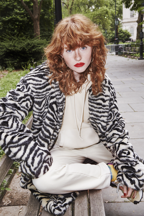 allison ponthier wearing a zebra coat and beige sweatsuit with tie dye socks and sneakers sitting on a park bench