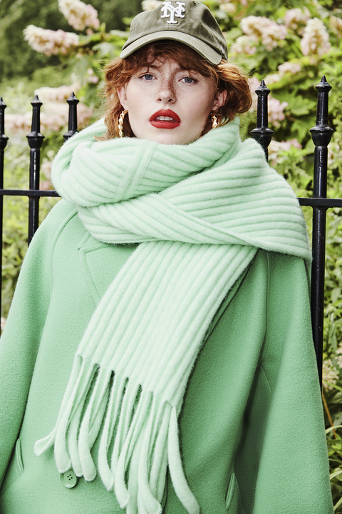 allison ponthier wearing a green coat and scarf with a baseball hat, gold earrings and a red lip
