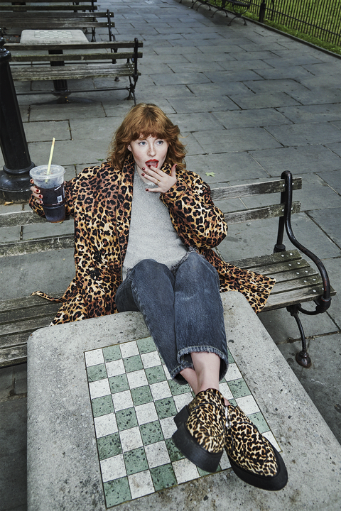 allison ponthier sitting on a park bench with her feet on a table wearing an animal pring coat and loafers and drinking a soda