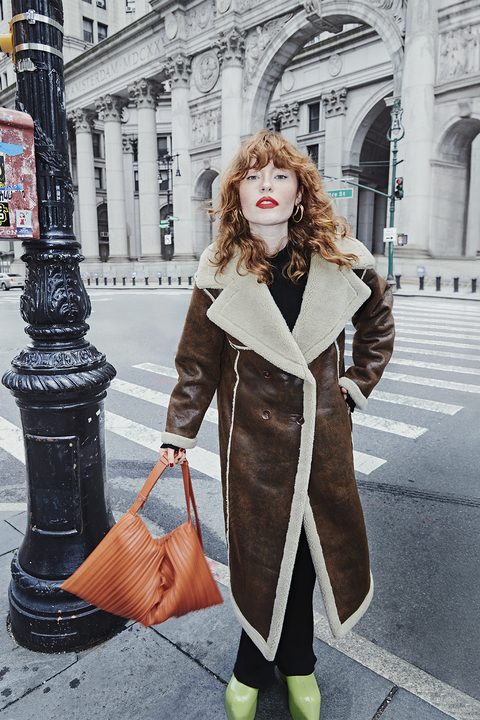 allison ponthier wearing a leather shearling coat and green shoes and holding a orange bag standing on the nyc street