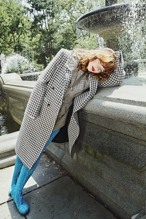 allison ponthier wearing a houndstooth coat and plaid blazer with sparkly blue leggings and shoes leaning on a stone fountain