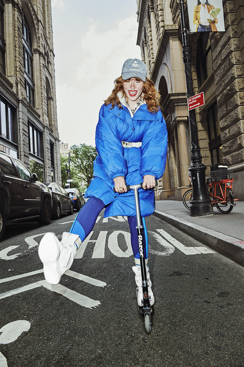 allison ponthier wearing a puffy blue coat, blue leggings and white sneakers riding a razor scooter in the streets of nyc