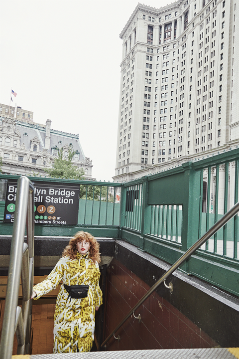 allison ponthier wearing a puffy yellow coat and black fanny pack walking up the subway stairs in nyc