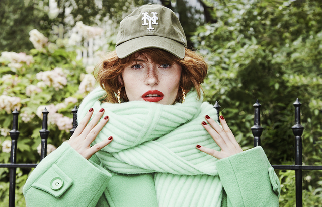 allison pontheir in a green coat and sweater and baseball cap