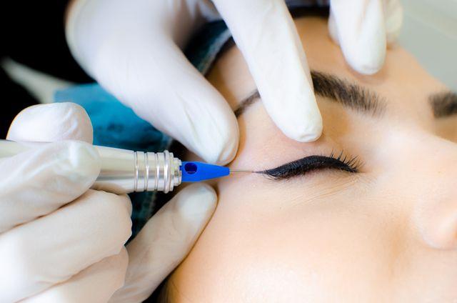 een vrouw krijgt een eyeliner tattoo