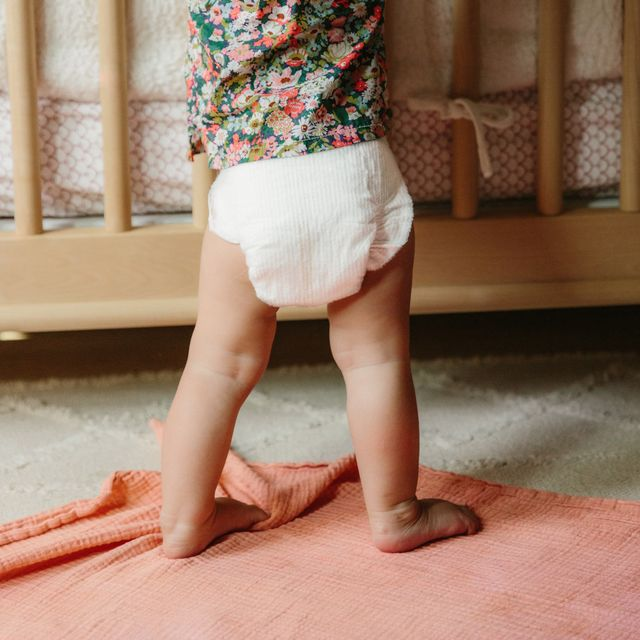 baby standing in front of crib with coterie toxin free diaper