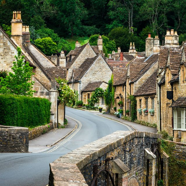 color image depicting a traditional english village in the cotswolds area of southwest england the cosy little brick cottages line the narrow road, and there is also a quaint bridge spanning a little stream room for copy space