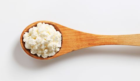 cottage cheese on a wooden spoon:best high protein foods