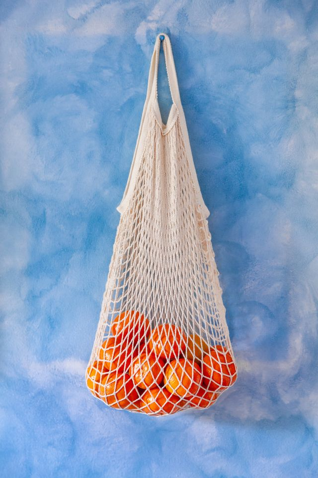 cotton mesh grocery shopping bag reusable containing tangerines, against blue wood background, close up
