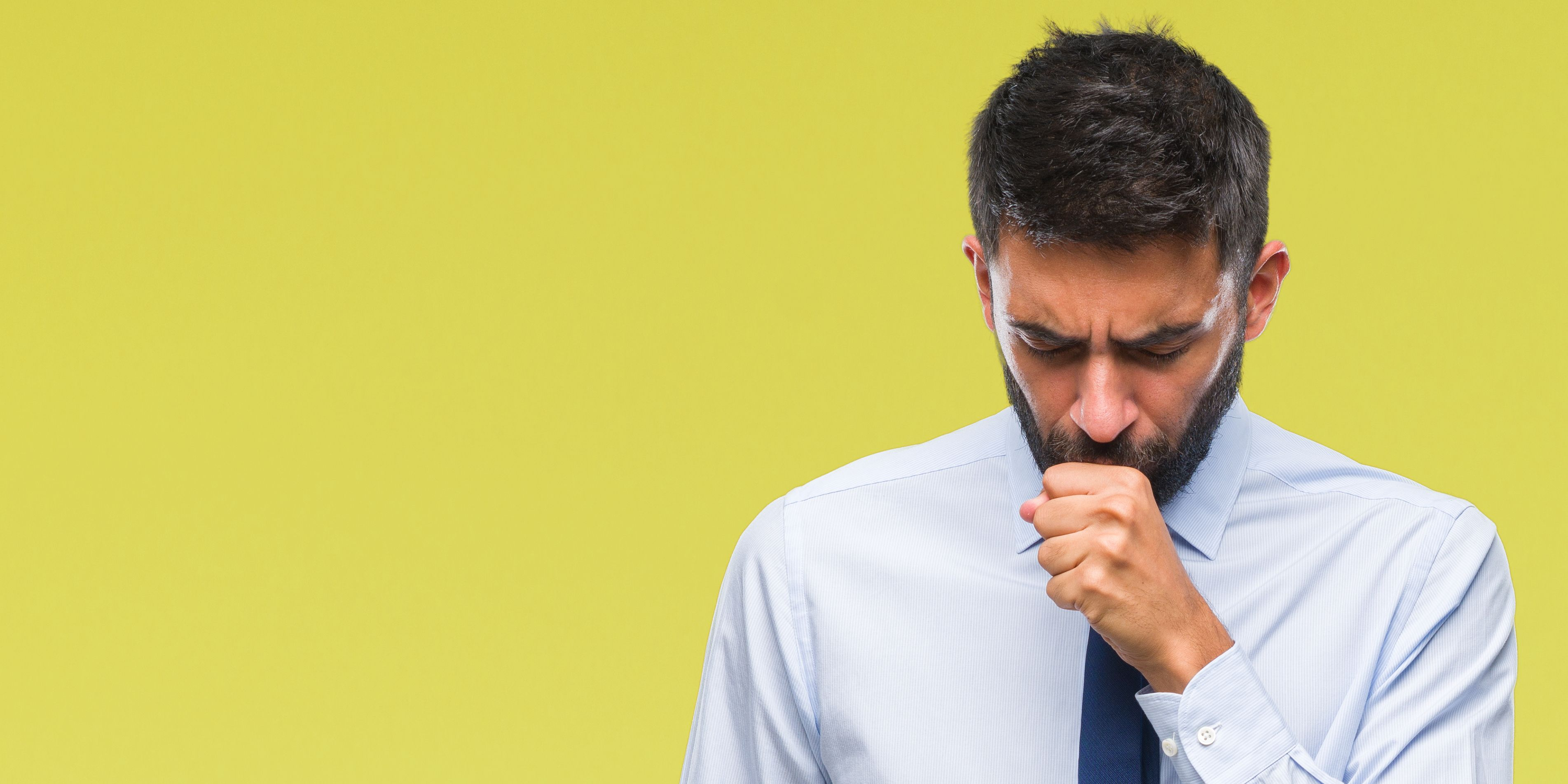 Adult hispanic business man over isolated background feeling unwell and coughing as symptom for cold or bronchitis. Healthcare concept.