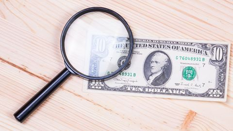 counterfeit money - cash note - magnifying glass